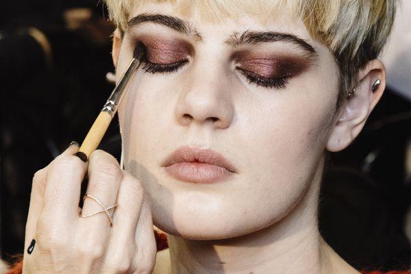 Makeup artist applying red eye shadow to model