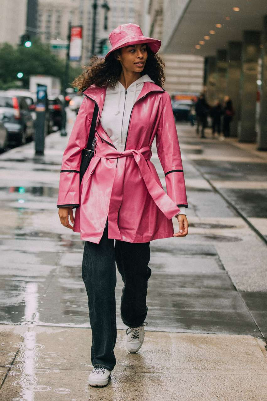 Woman wears a pink rain hat and raincoat while walking on a wet sidewalk