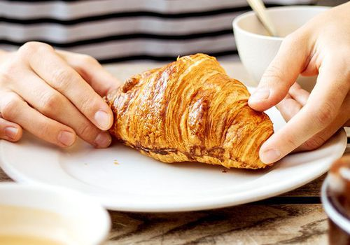 Hands picking up a croissant that is on a plate