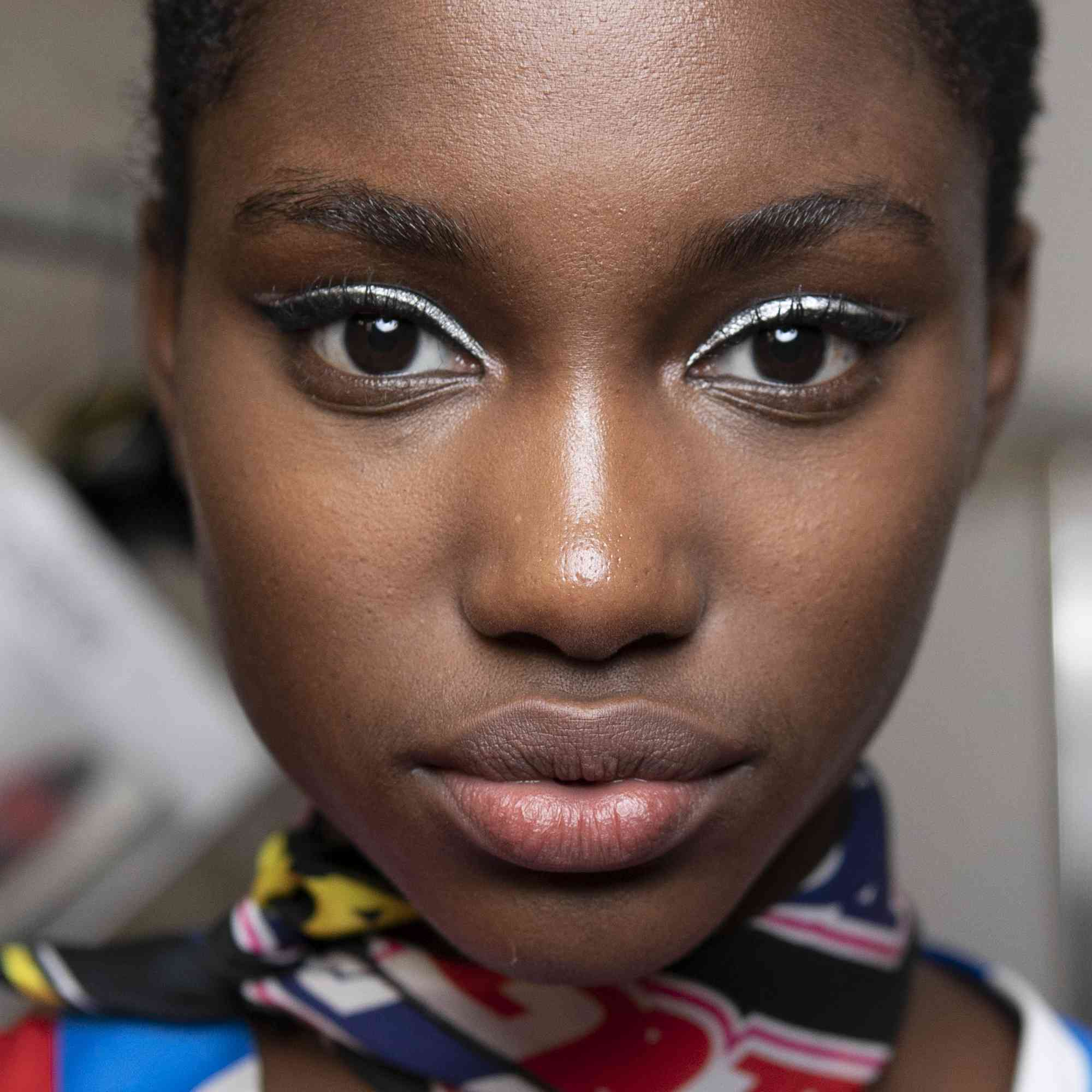 model backstage at NYFW with blue eyeliner and long lashes