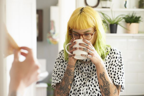 Young woman drinking coffee in her kitchen