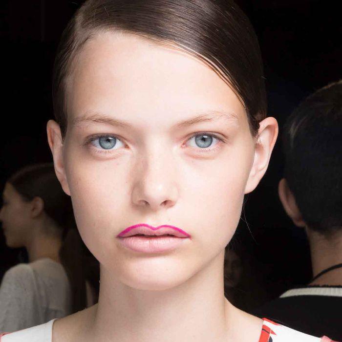 Model wearing half-done hot pink lip liner