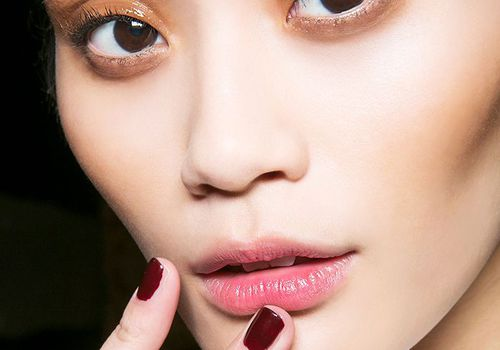 Model with burgundy nail polish touching her face