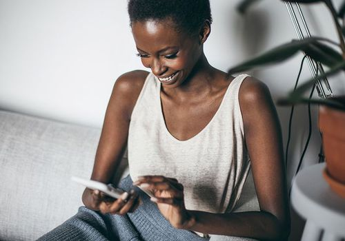 girl laughing on couch looking at phone