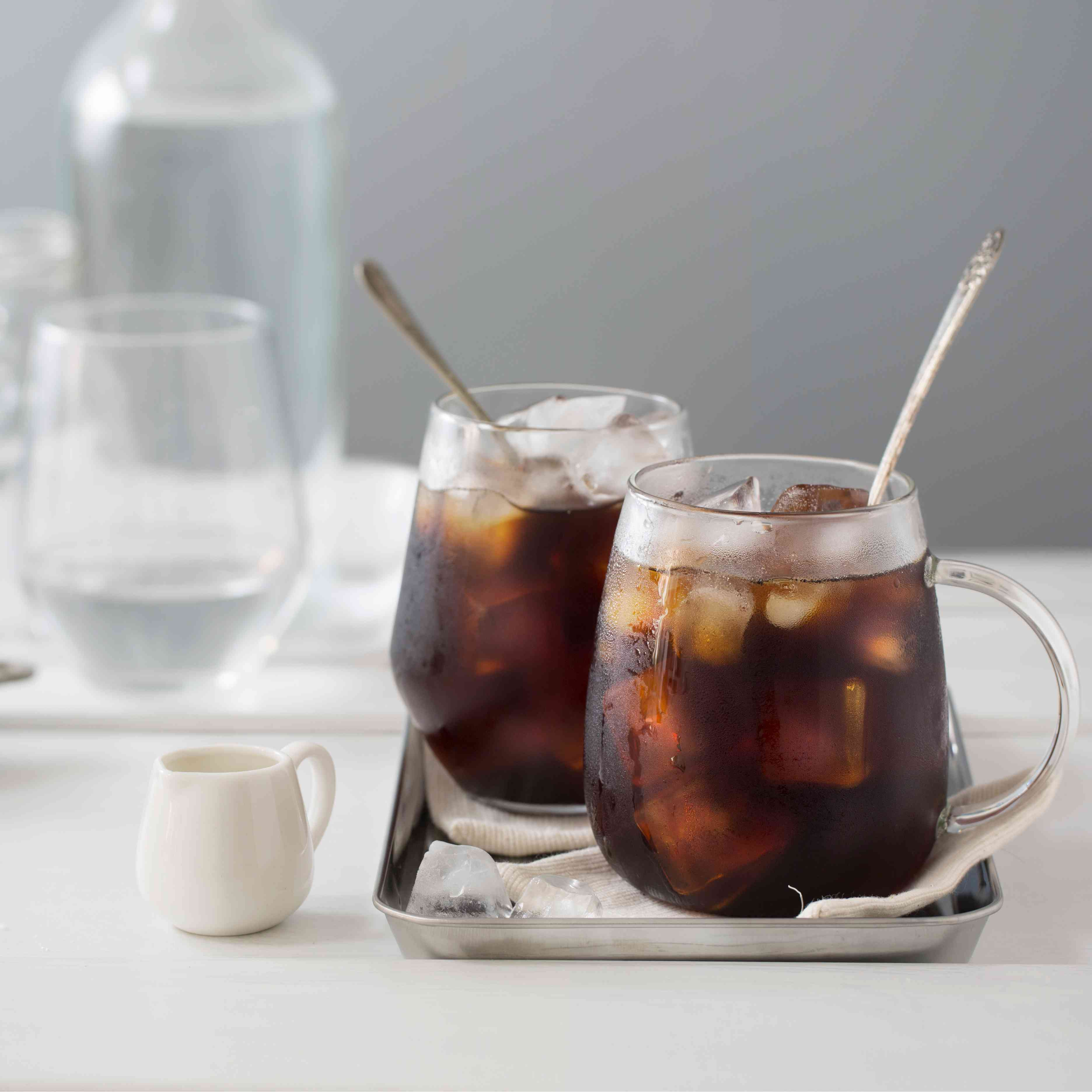 Beverages in clear glasses with ice cubes