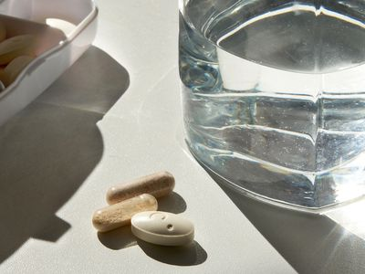 Pills on a table with a glass of water
