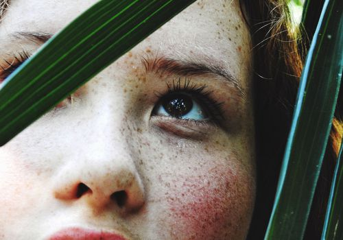 woman with freckles looking up through leaves of tree