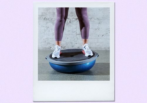 Woman balancing on a Bosu ball.
