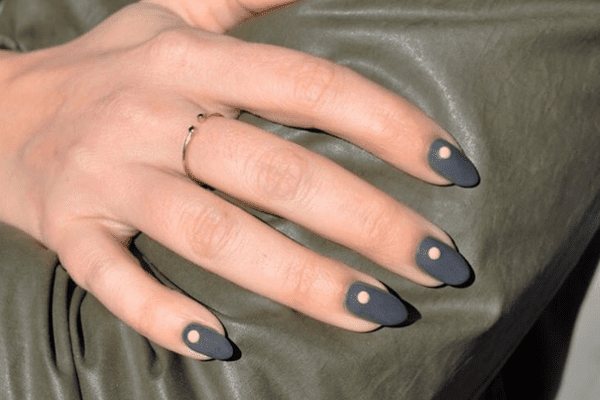 Charcoal gray nails with a nude dot on each.