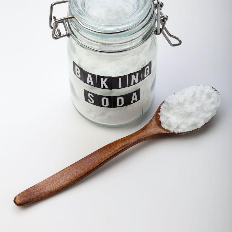 Baking soda in a lidded mason jar and wooden spoon