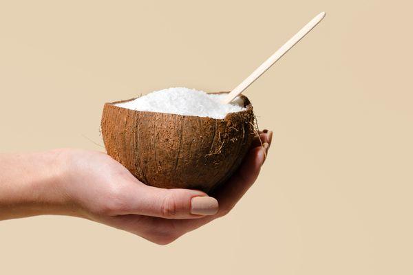 woman holding split coconut