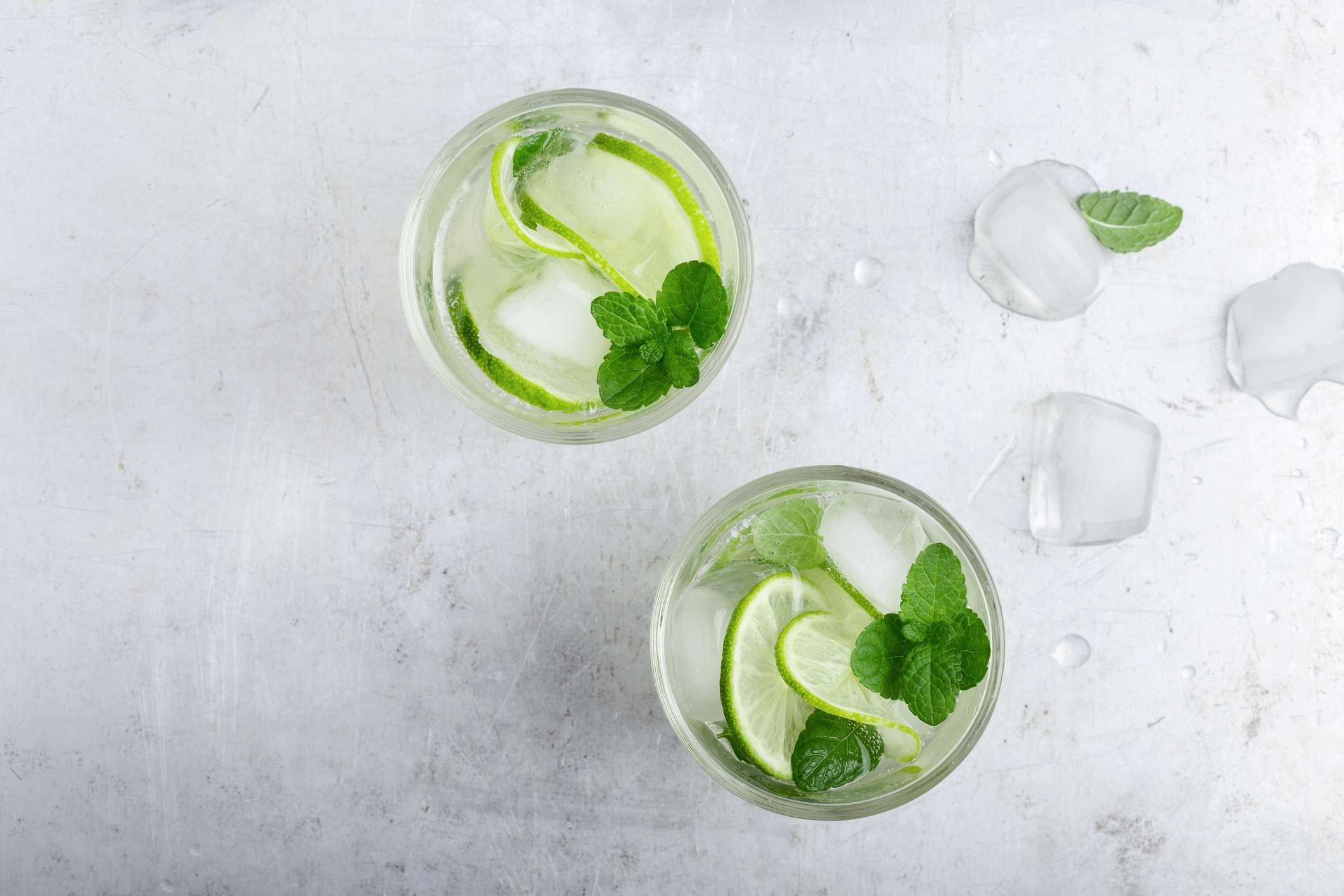 Two glasses of water with fresh lime, sitting on a table.