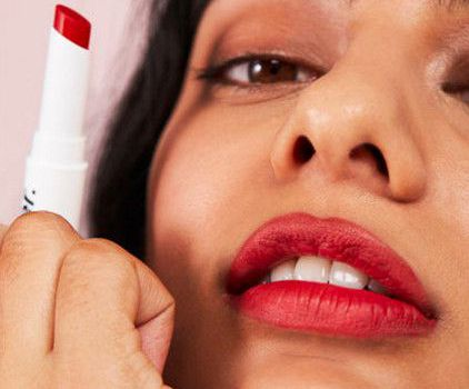 woman with red lipstick holding glossier lip stick