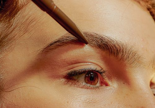 Woman penciling in her brows.
