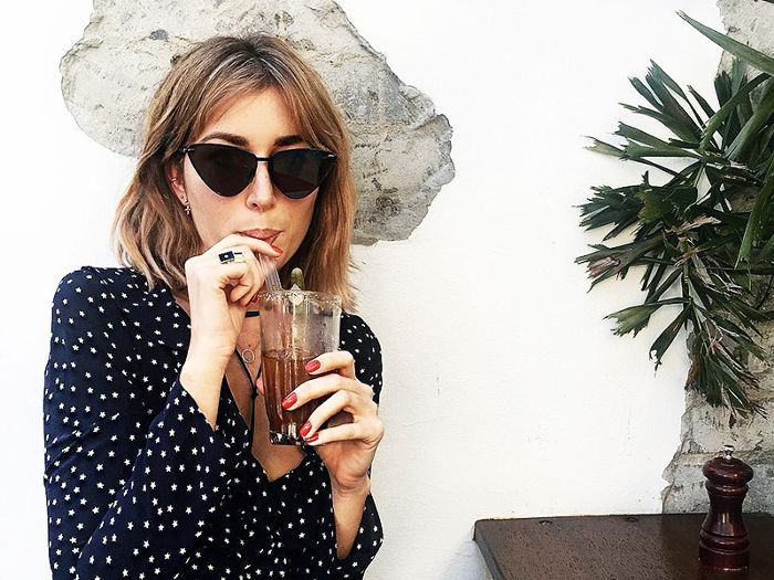 Woman wearing sunglasses and sipping on a drink