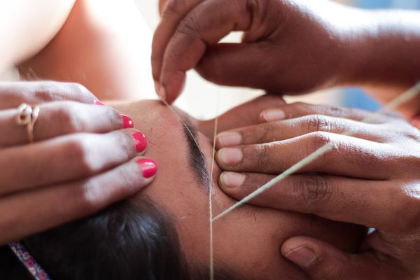Hands Of Beautician Threading Woman Eyebrows