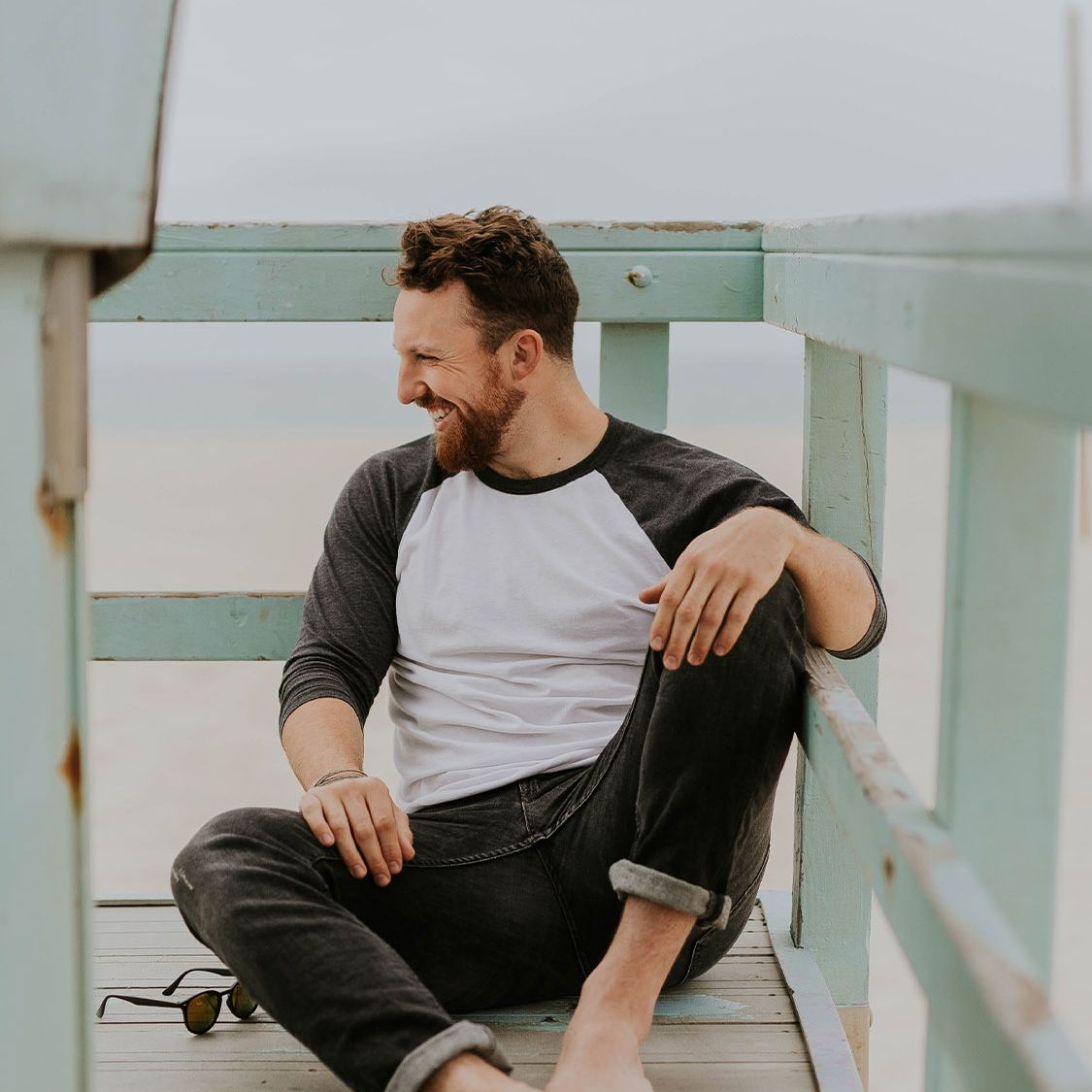 man sitting on beach and smiling