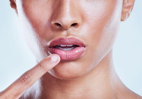 A woman applies lip balm.