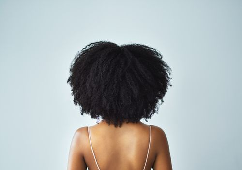 Back view of a woman with curly/kinky hair, from the waist up
