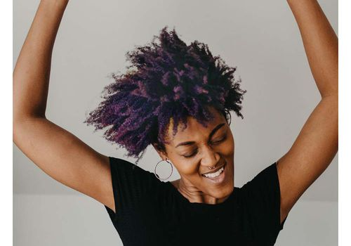 person with purple hair dancing happy