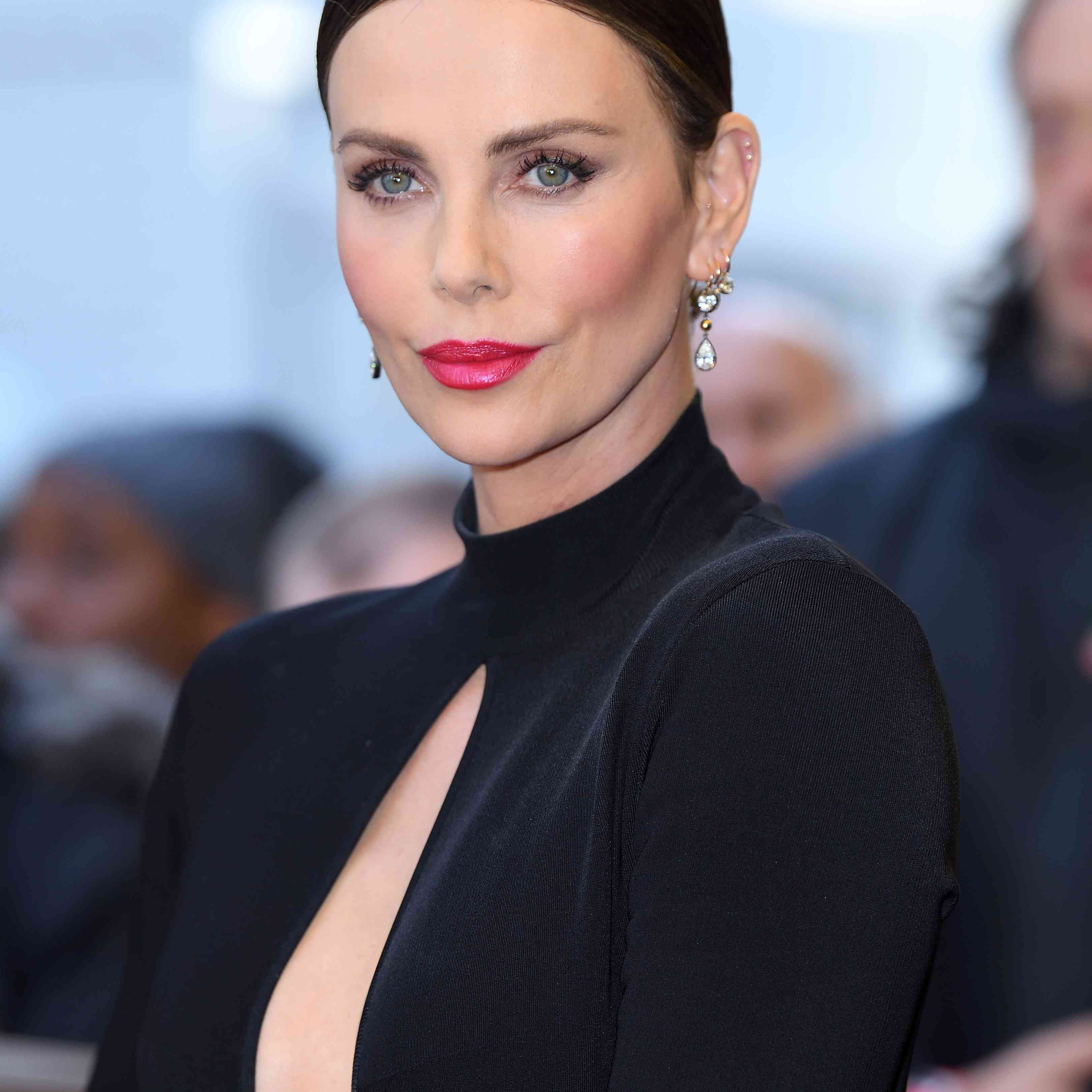 Charlize Theron wearing magenta lipstick and a black dress