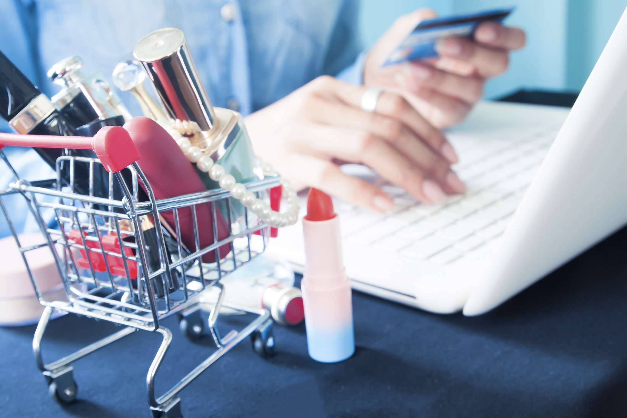 Woman On A Computer With Beauty Products Around