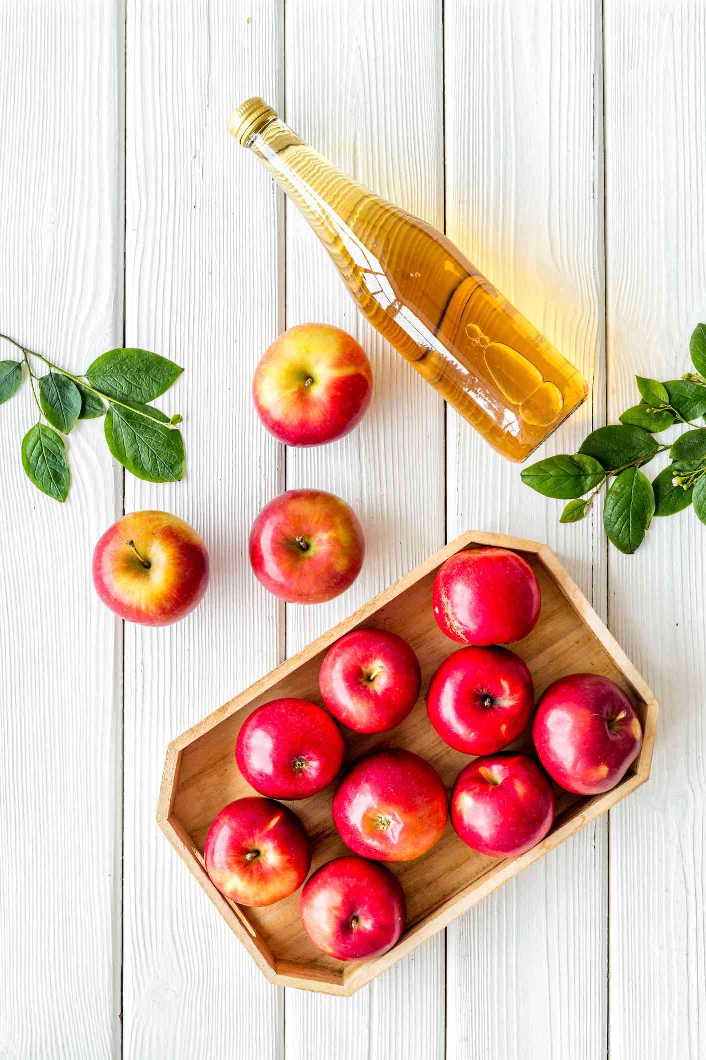 bottle of apple cider vinegar with apples