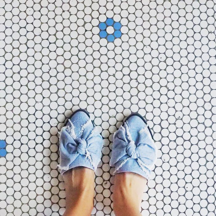 Person wearing denim shoes standing on tiled floor