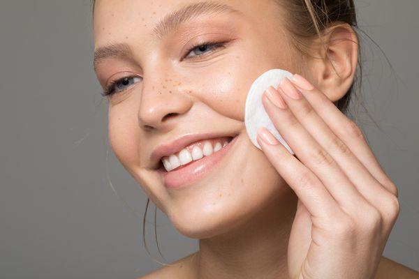 Closeup of woman applying toner to cheek