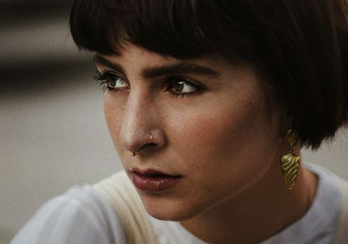Woman with short brown hair and a nose ring