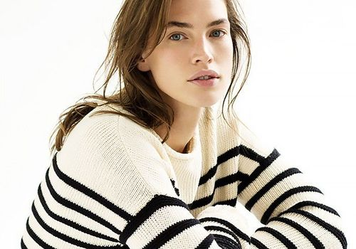 Woman with wavy hair wearing striped sweater