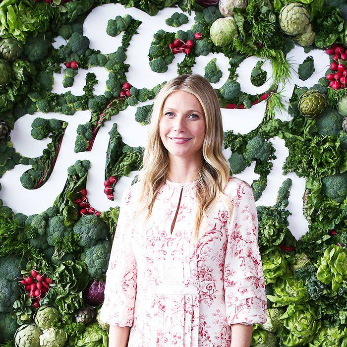 "Gwyneth Paltrow standing in front of a wall of plants that reads ""In Goop Health"""