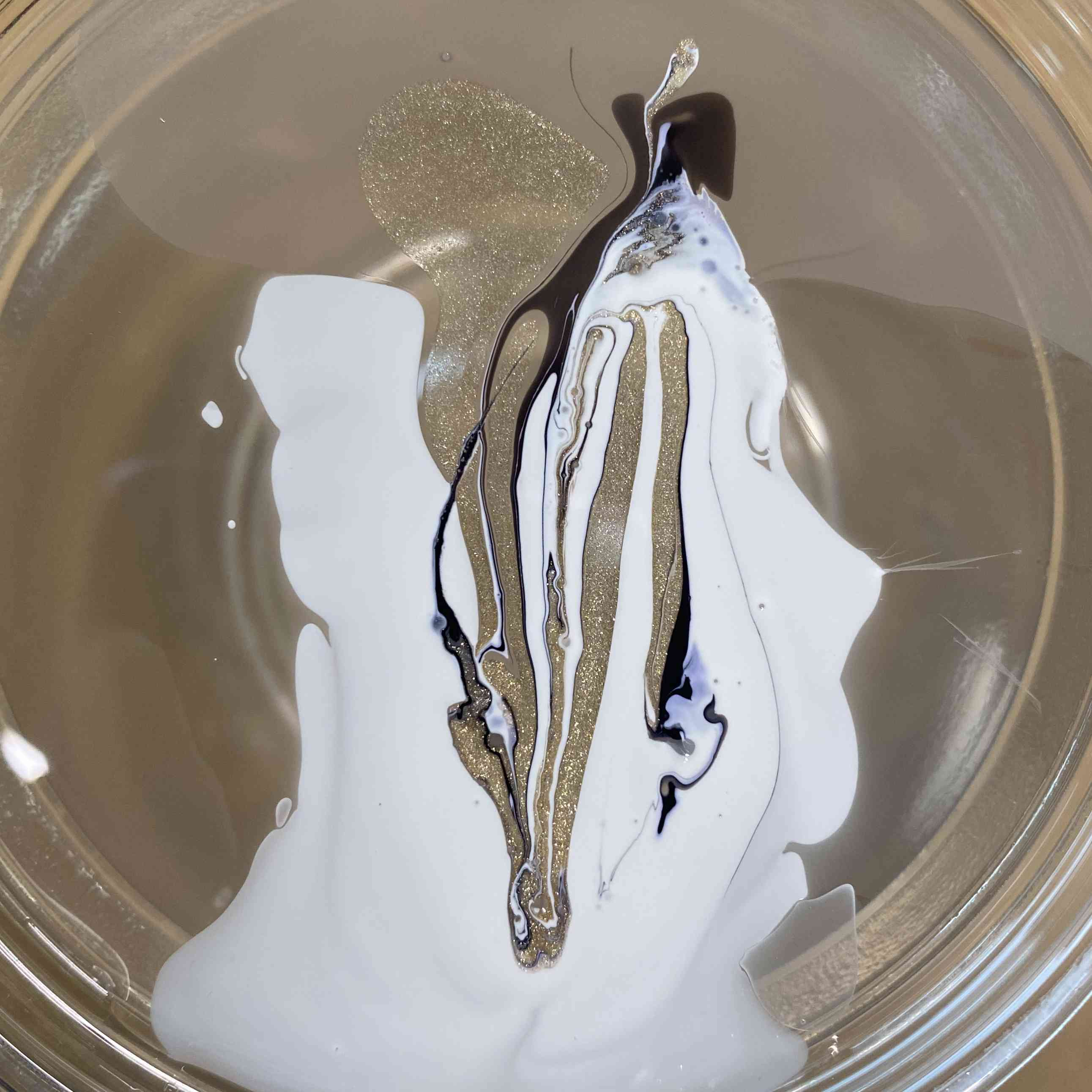 Swirled nail polish in a cup of water.