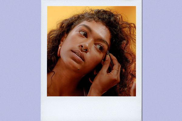 woman plucking eyebrows in mirror