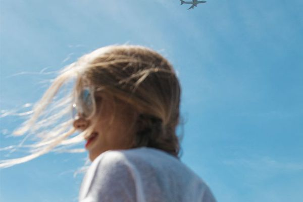 Woman with hair blowing and blue sky with plane flying overhead