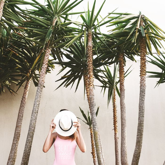 Australian Beauty Brands: Woman with palm trees in pink swimsuit