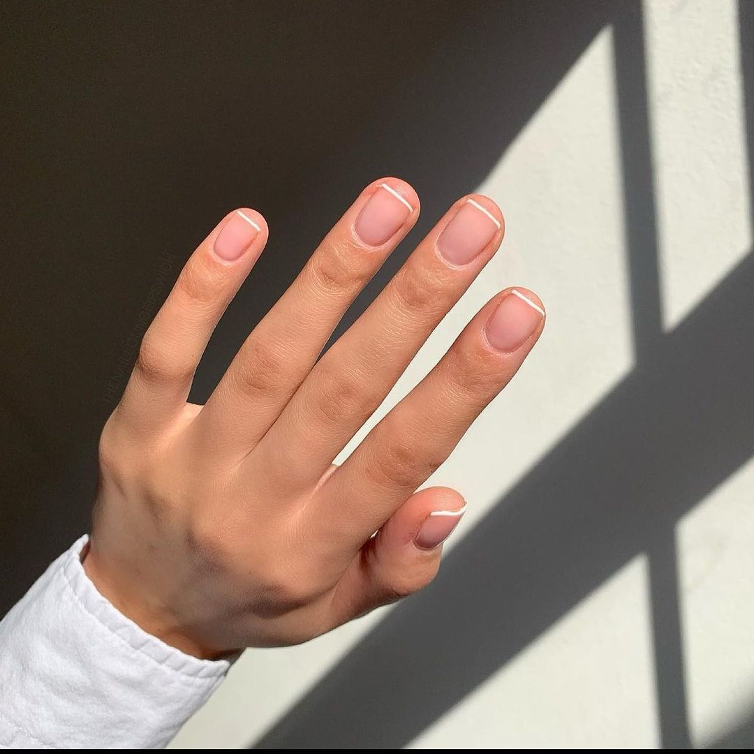 Person with fine white French tips