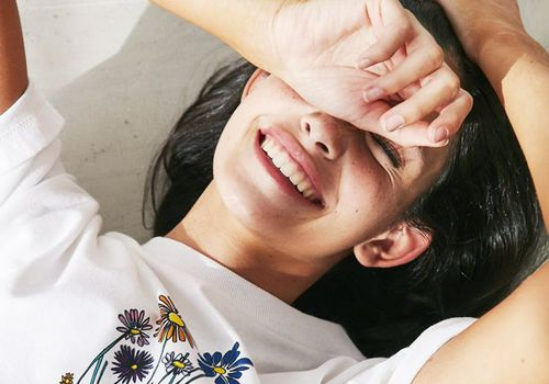 Woman laying on the ground smiling with hand over her eyes