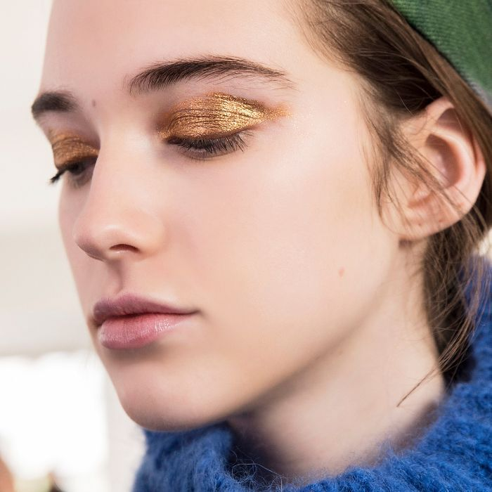 Woman in a blue sweater with bright gold metallic eye makeup