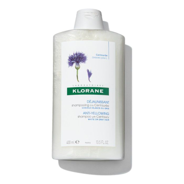 White bottle of shampoo with a purple flower on the label.