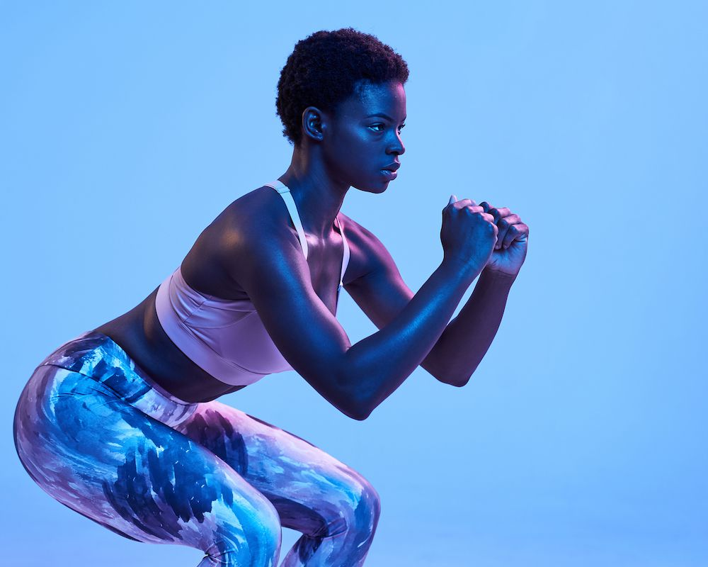 woman performing a squat against blue background