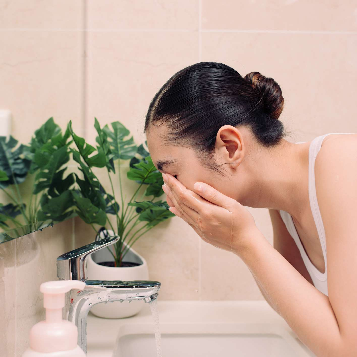Woman washing her face and neck in the mirror