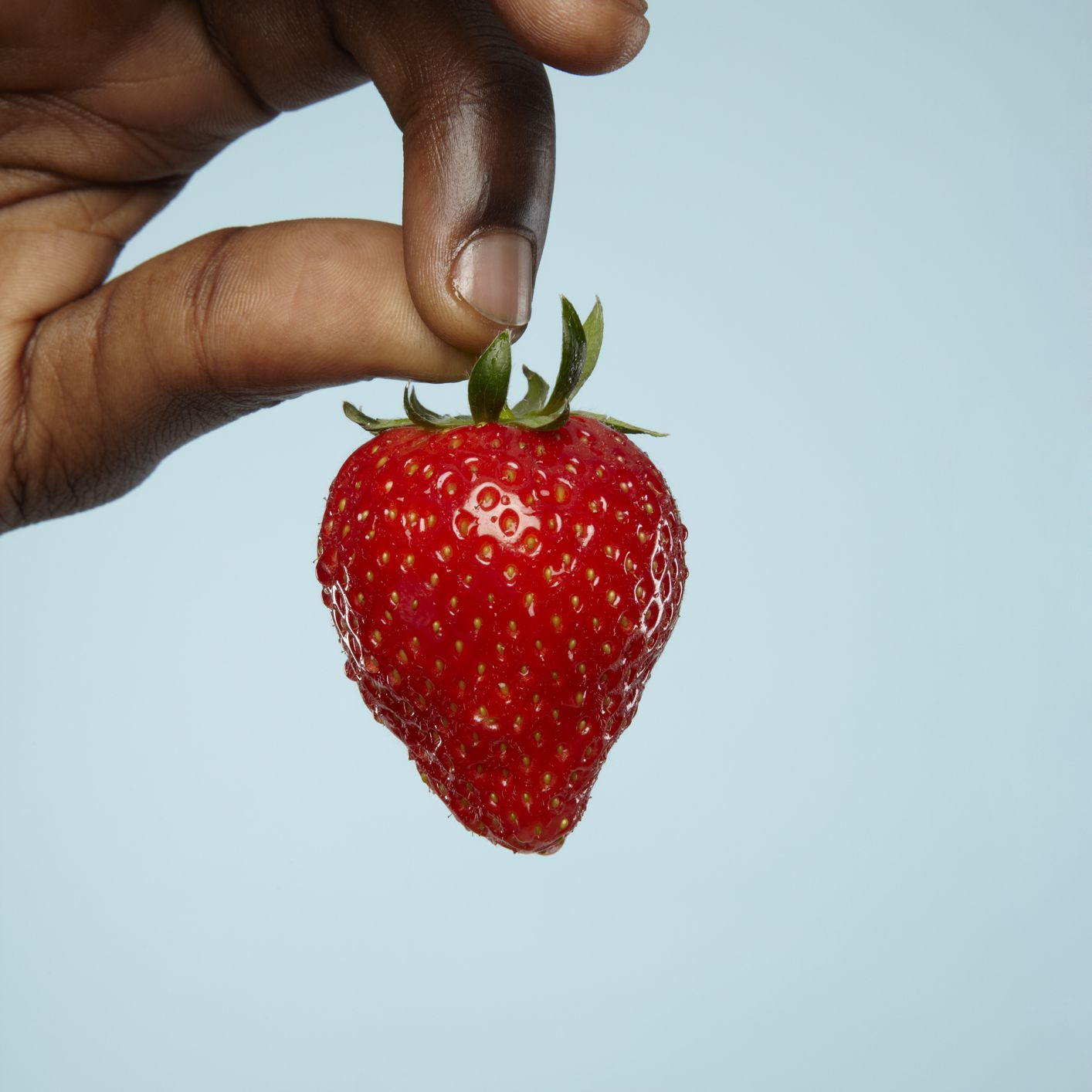 closeup of strawberry in fingers
