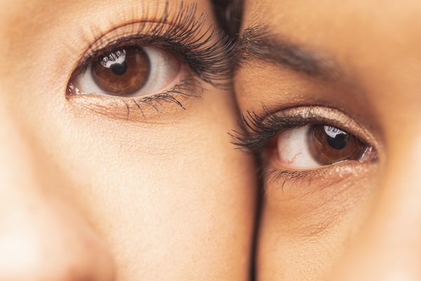 two women with long eyelashes looking at camera