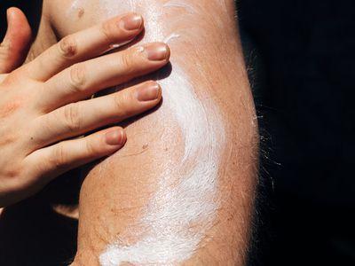 man applying body lotion