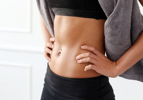 An athletic woman wearing black workout gear and a belly button ring