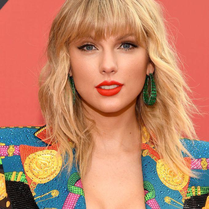 Taylor Swift wavy, layered mid-length hair with bangs