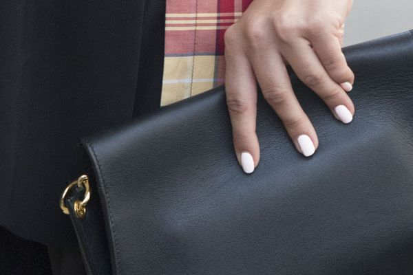 woman with white finger nails holding a purse