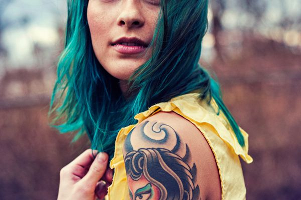 Girl with blue hair and tattoos looking over