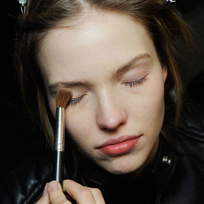 Woman applying eyeshadow with makeup brush